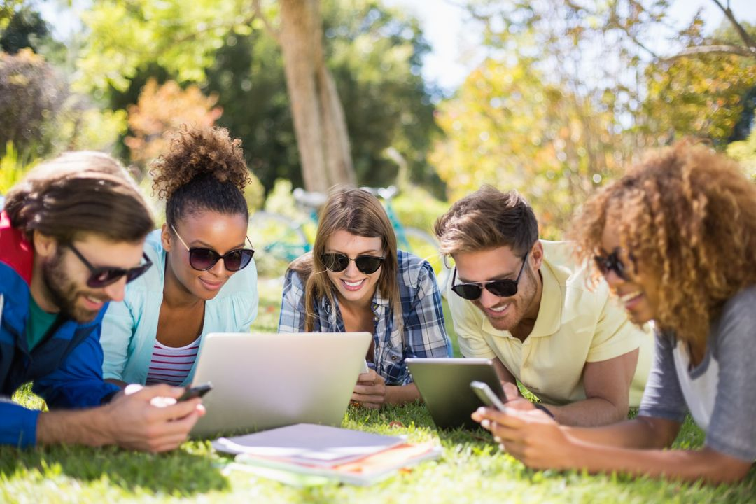 Group of friends using laptop, mobile phone and digital tablet in park Free Stock Images from PikWizard