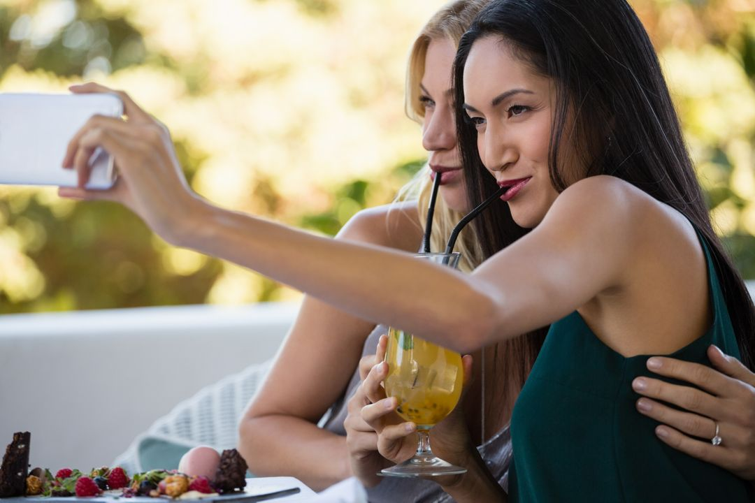 Female friends taking selfie while having drinks at restaurant Free Stock Images from PikWizard