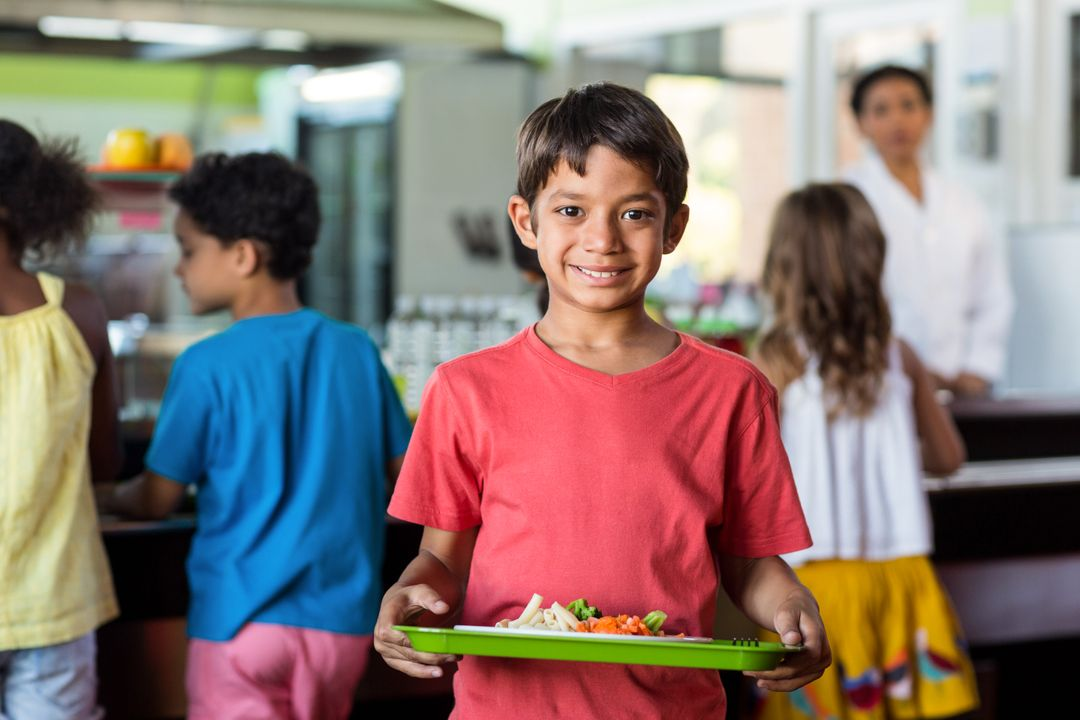 Portrait of smiling schoolboy holding food tray in canteen against classmates