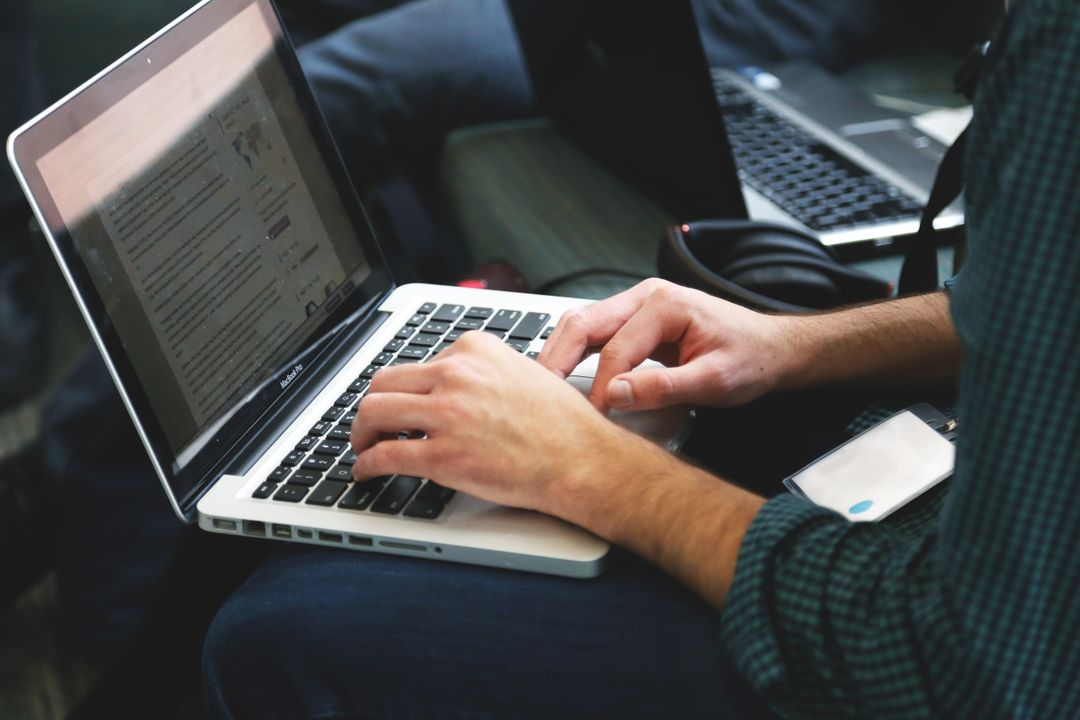 Side image of a person typing copy on a laptop