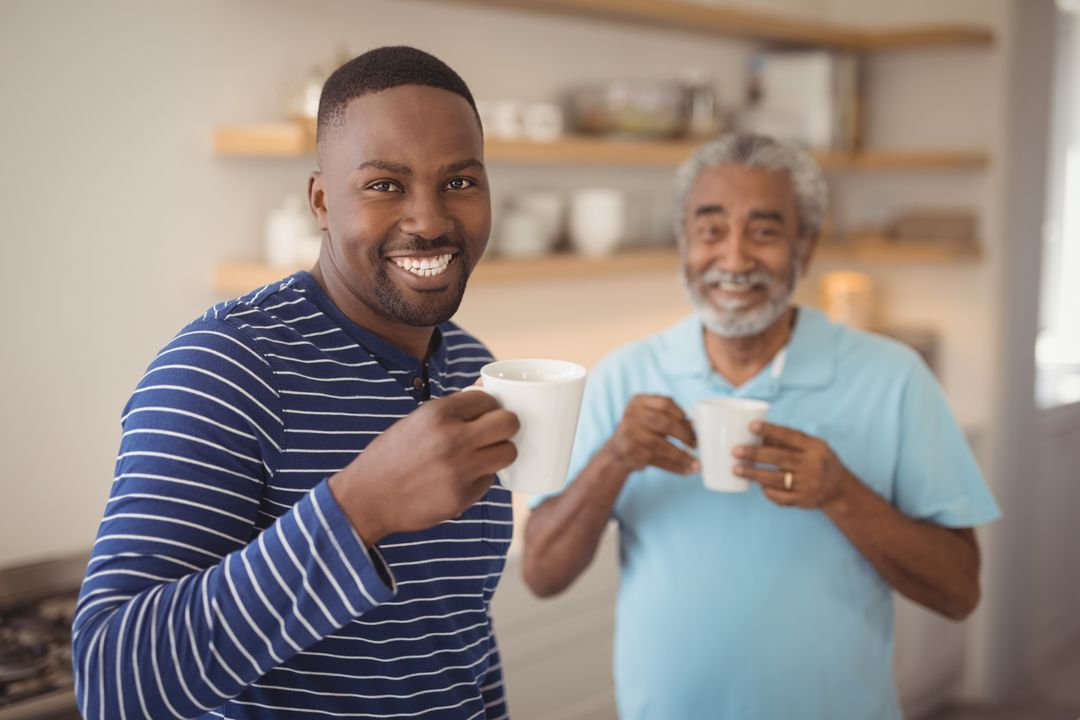 Portrait of smiling father and son having cup of coffee in kitchen at home Free Stock Images from PikWizard