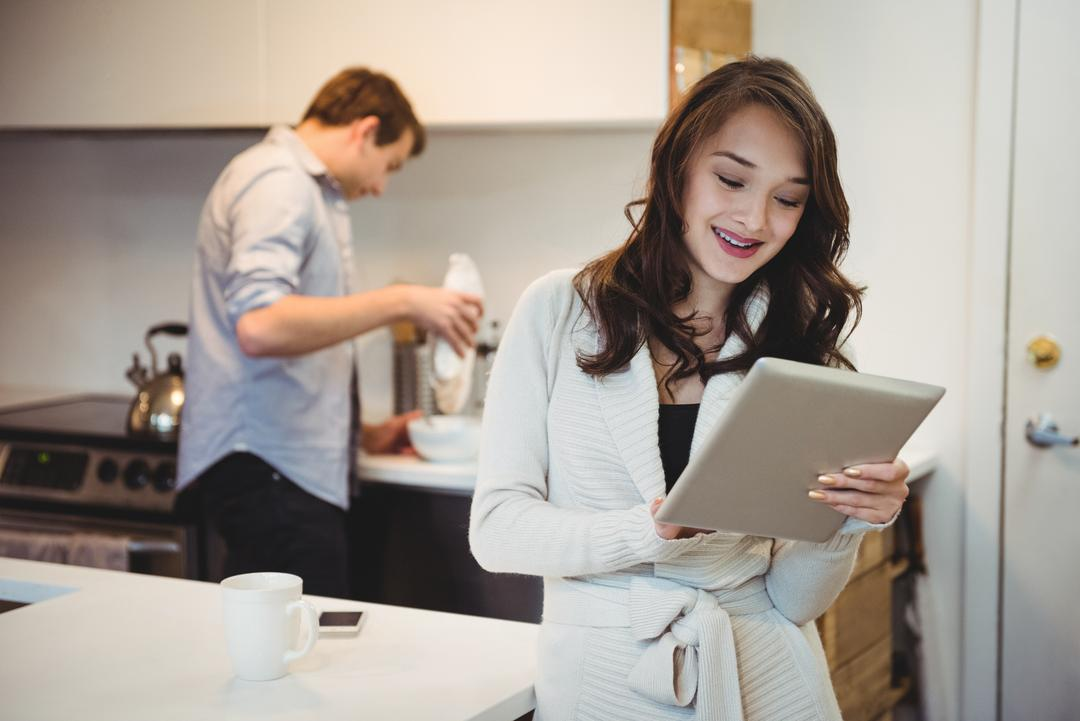 Woman using digital tablet while man working in background at kitchen