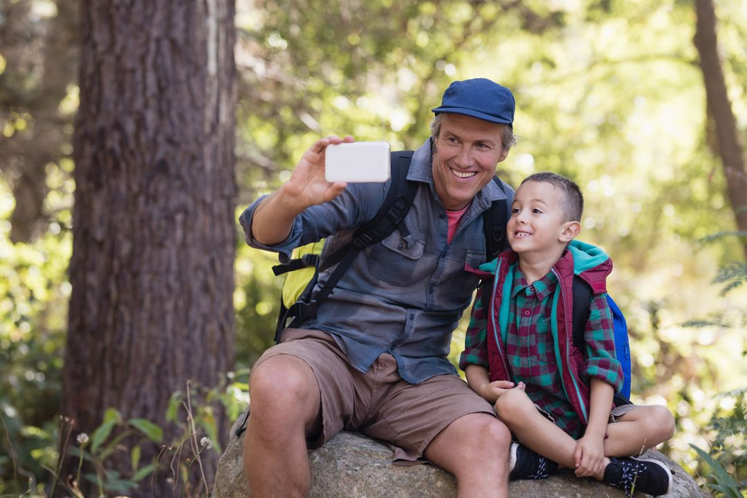 Happy father sitting with boy on rock taking selfie from mobile phone in forest Free Stock Images from PikWizard