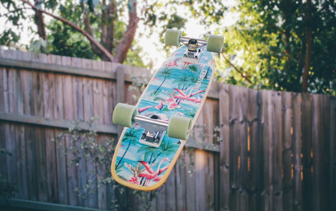 Colorful colors on skateboard in mid air with a fence in the background