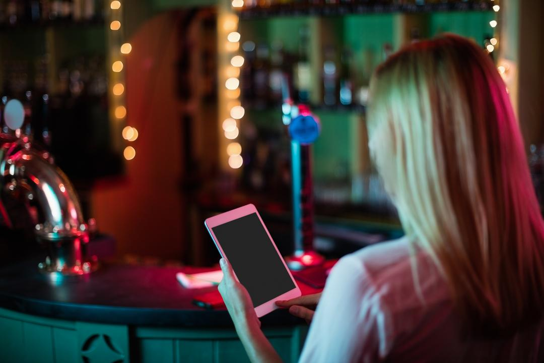 Rear view of waitress using a digital tablet in bar