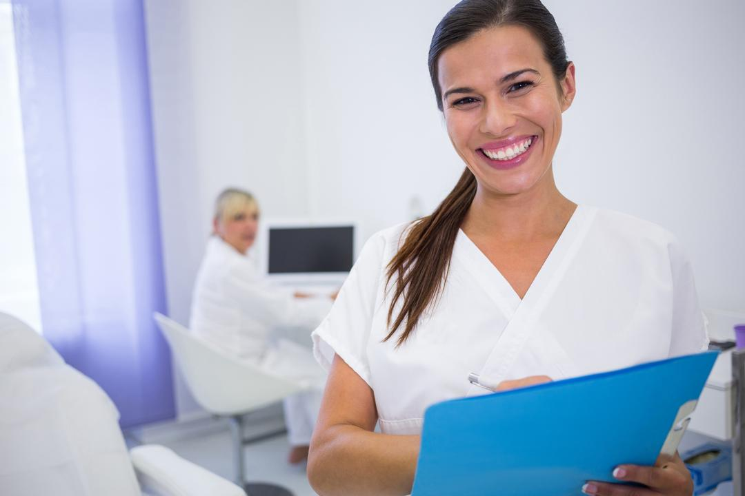 Portrait of smiling dentist writing a medical report in clinic Free Stock Images from PikWizard