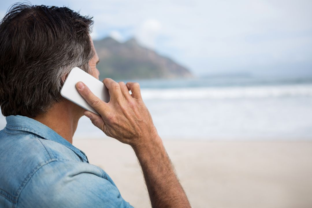 Man talking on mobile phone on beach during winter Free Stock Images from PikWizard