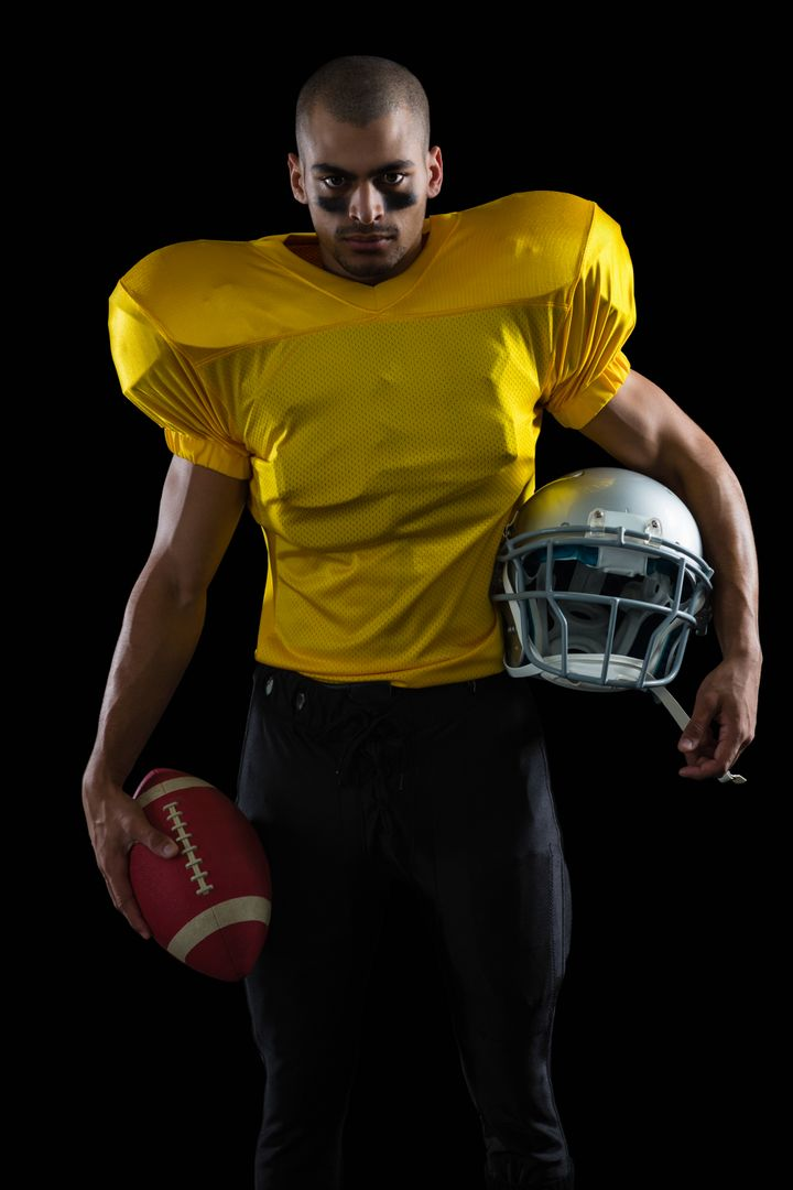 Portrait of American football player holding a ball and head gear Free Stock Images from PikWizard