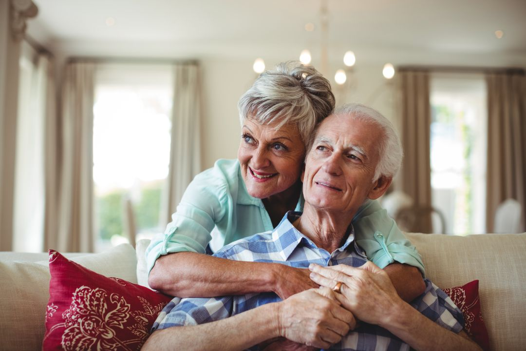 Senior couple relaxing on sofa in living room at home Free Stock Images from PikWizard