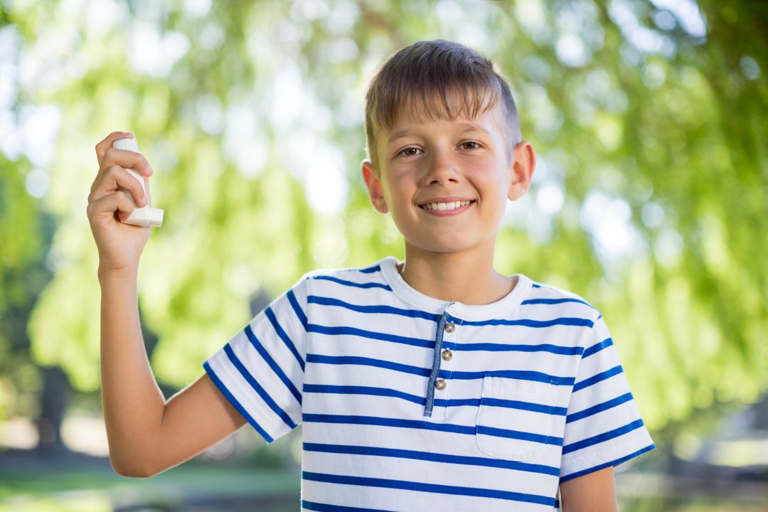 Boy holding asthma inhaler in park on a sunny day Free Stock Images from PikWizard