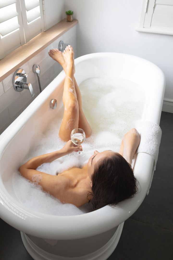 Beautiful woman having champagne while taking bubble bath in bathroom at home