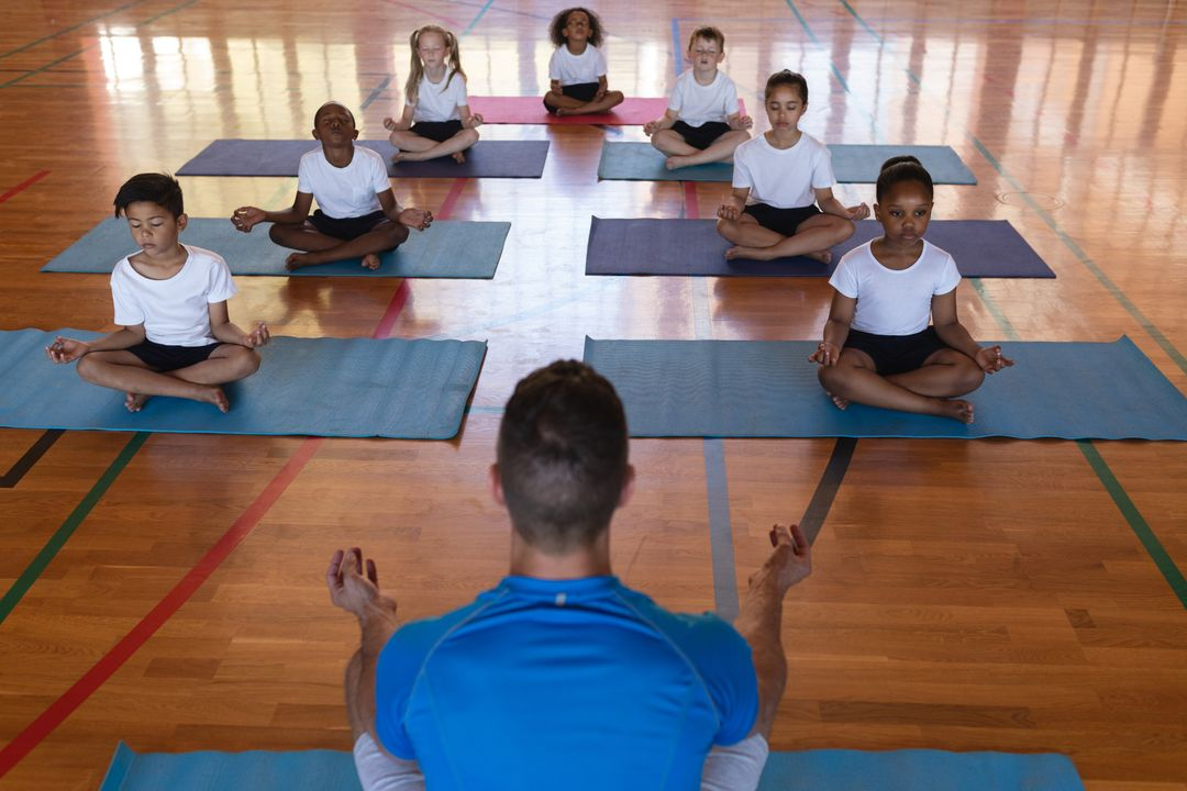 High angle view of yoga teacher teaching yoga to school kids in school gymnast Free Stock Images from PikWizard