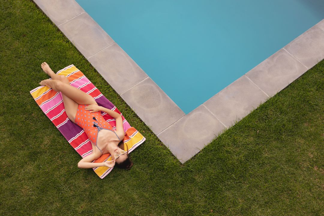 High angle view of Caucasian woman in swimwear relaxing near poolside in the backyard
