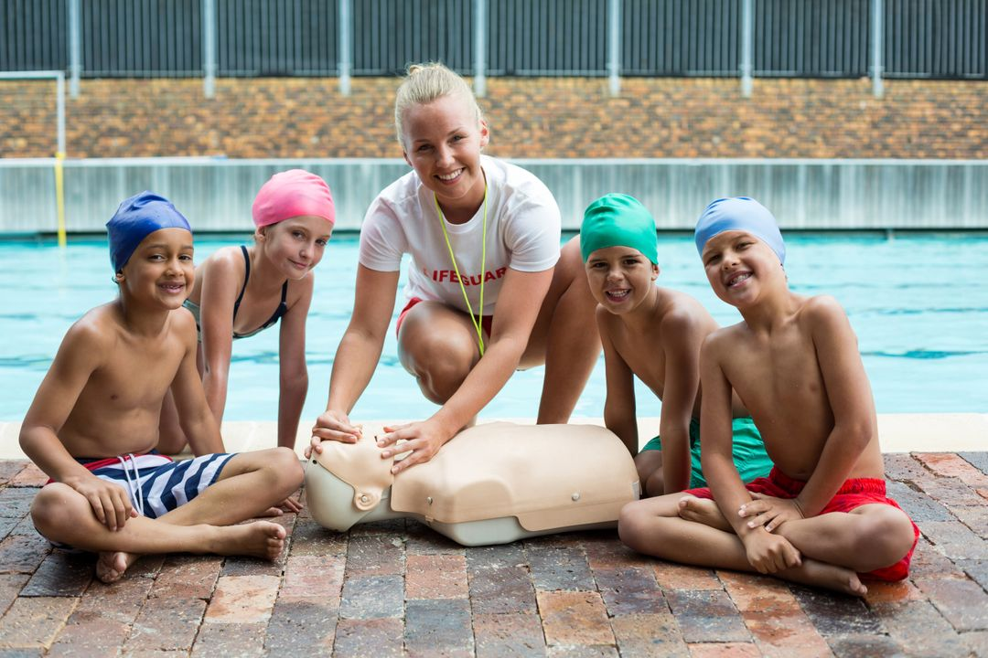 Portrait of happy children and instructor during rescue training at poolside Free Stock Images from PikWizard