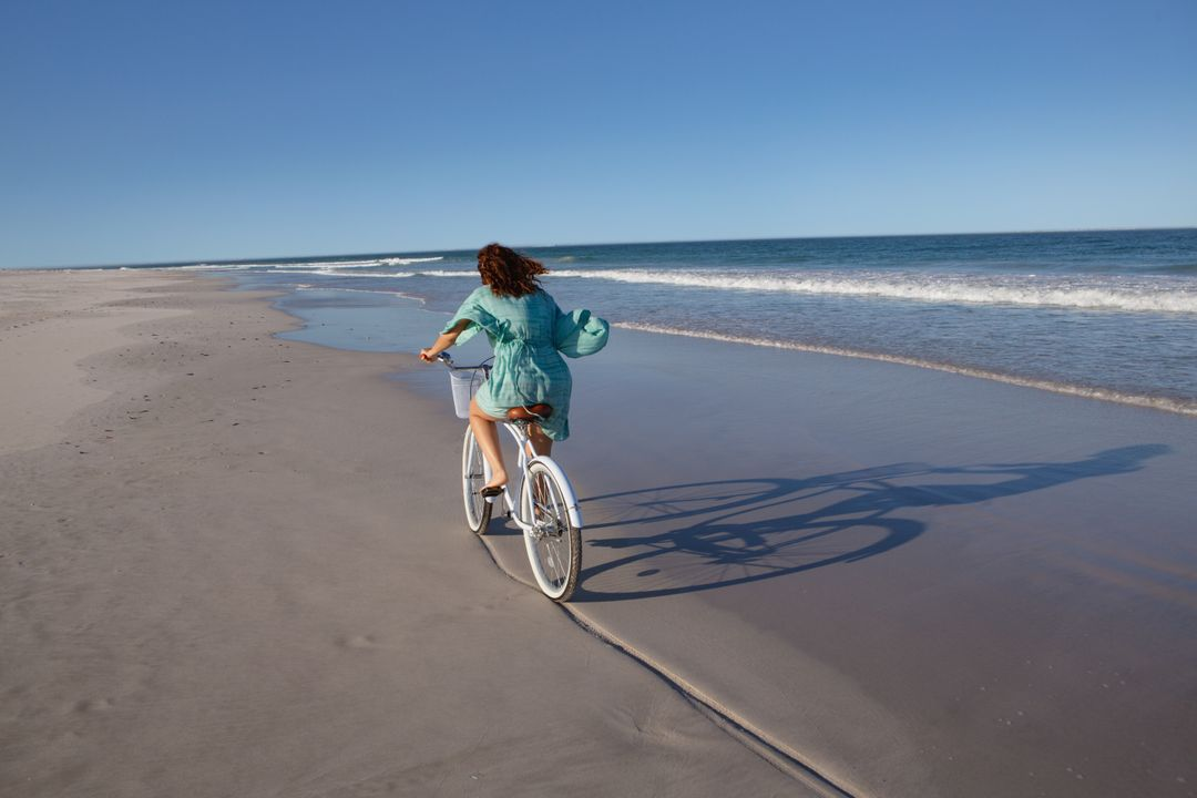 Rear view of mixed race woman riding bicycle on beach in the sunshine Free Stock Images from PikWizard