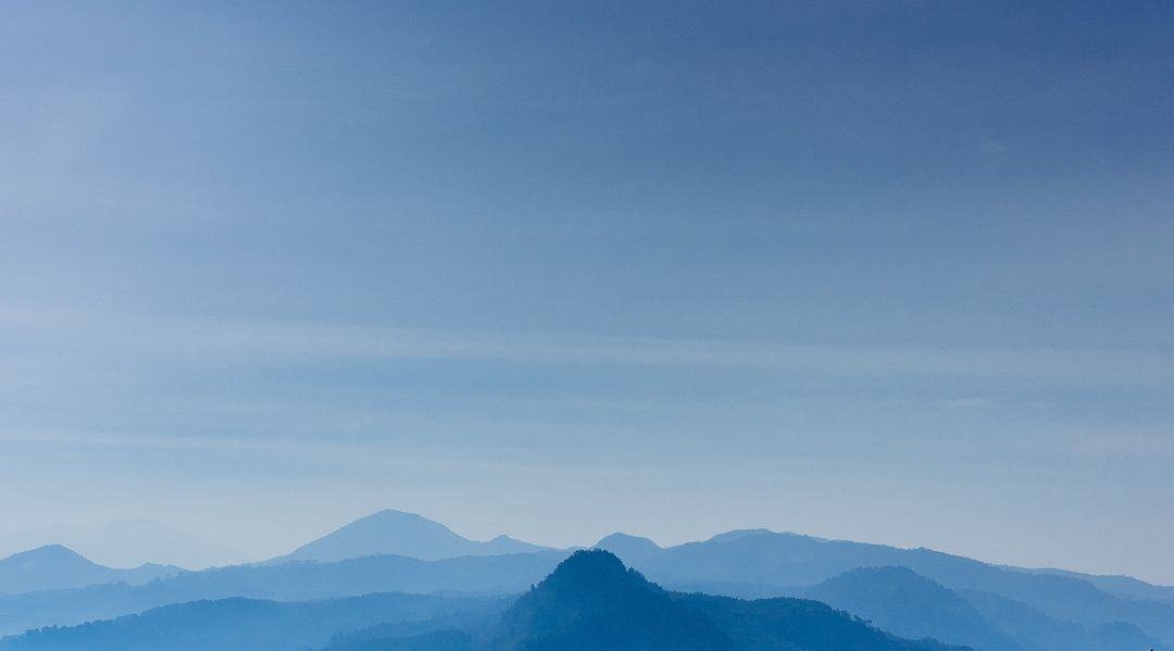 Landscape image of blue mountain tops with a blue sky in the background