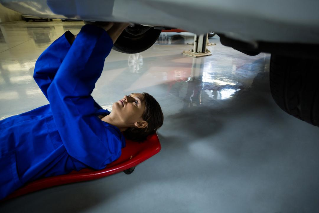 Female mechanic repairing a car in repair garage