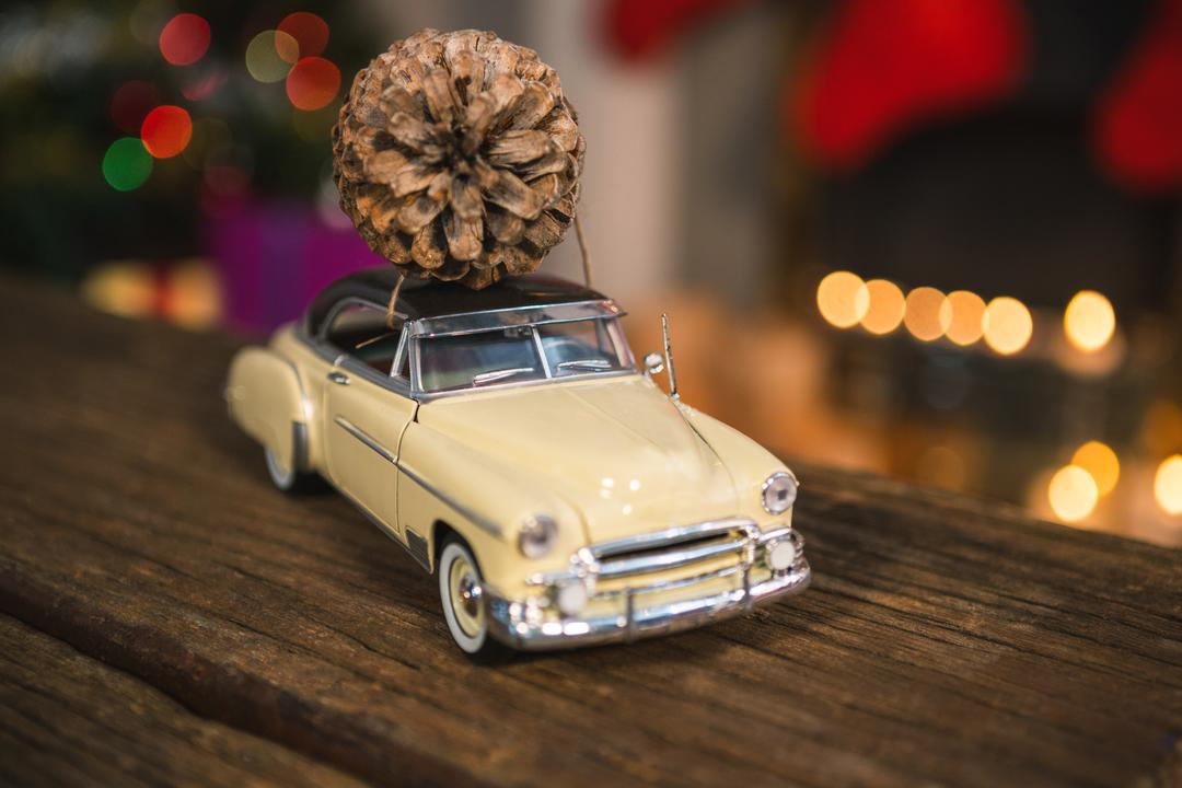 Toy car with pine cone on wooden table during christmas time
