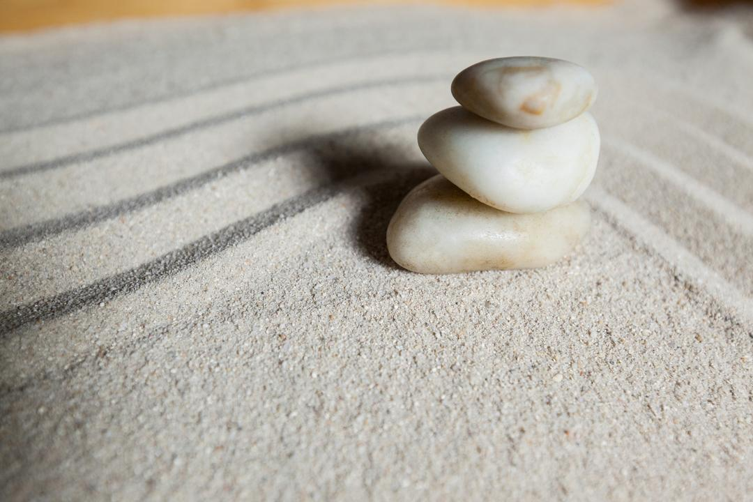 Stack of white pebbles stone on a sand