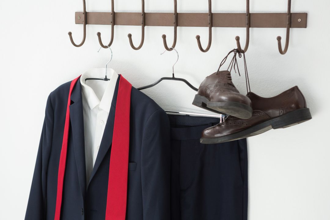Close-up of full suit and shoes hanging on hook against white wall