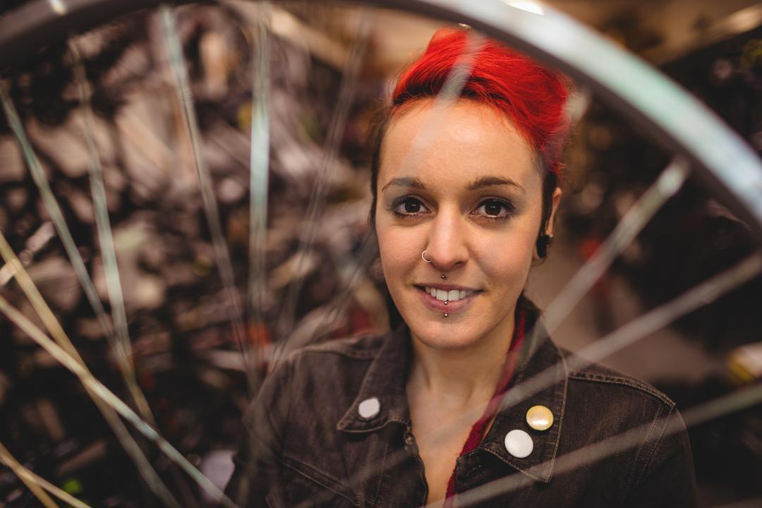 Portrait of mechanic examining a bicycle wheel in workshop Free Stock Images from PikWizard