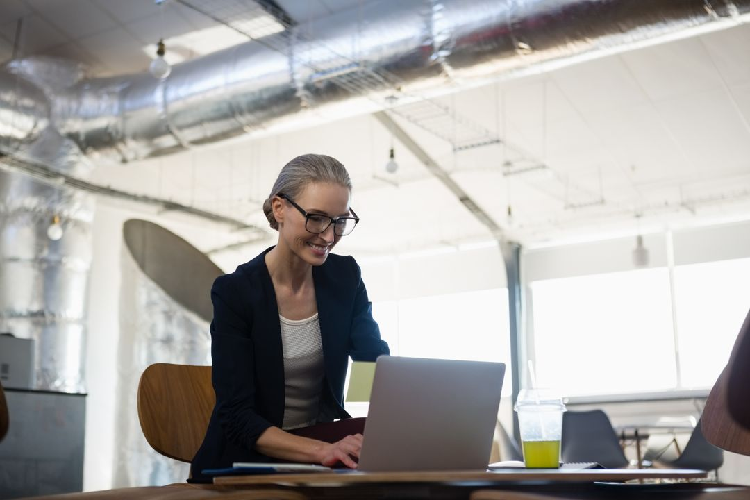 Smiling young businesswoman using laptop in creative office