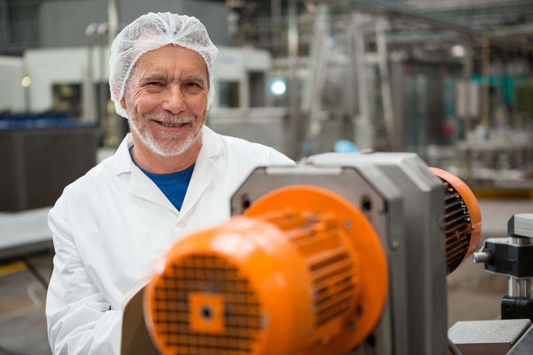 Portrait of happy male worker standing by machines at cold drink factory