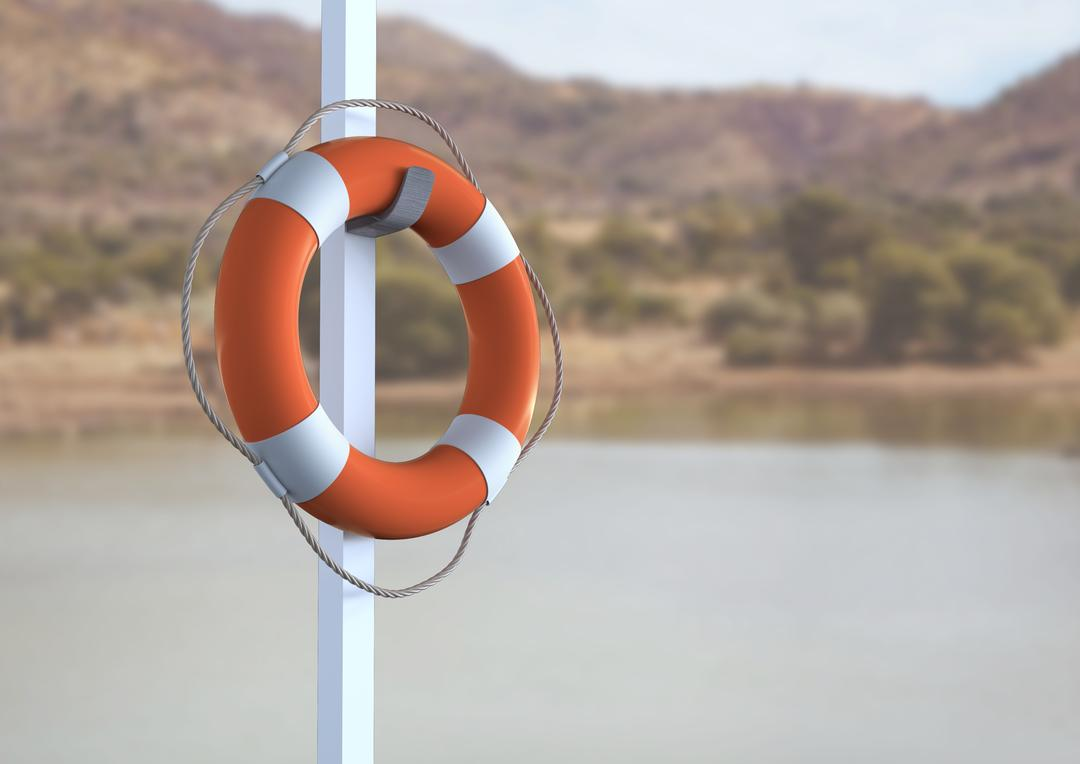 Close up of lifebuoy hanging on pole against lake side