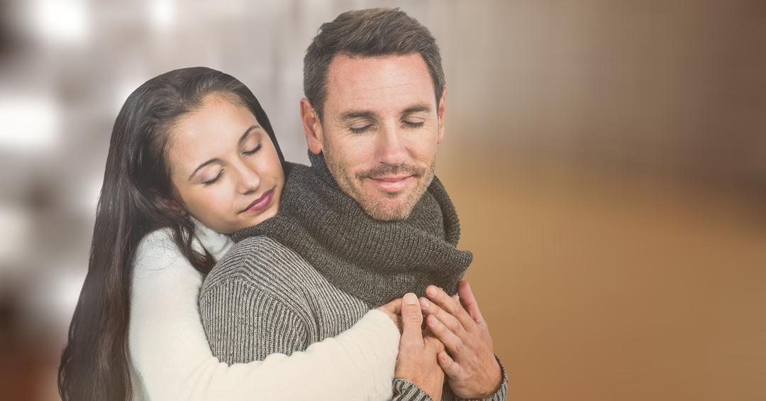 Loving couple in warm clothes embracing over blur background