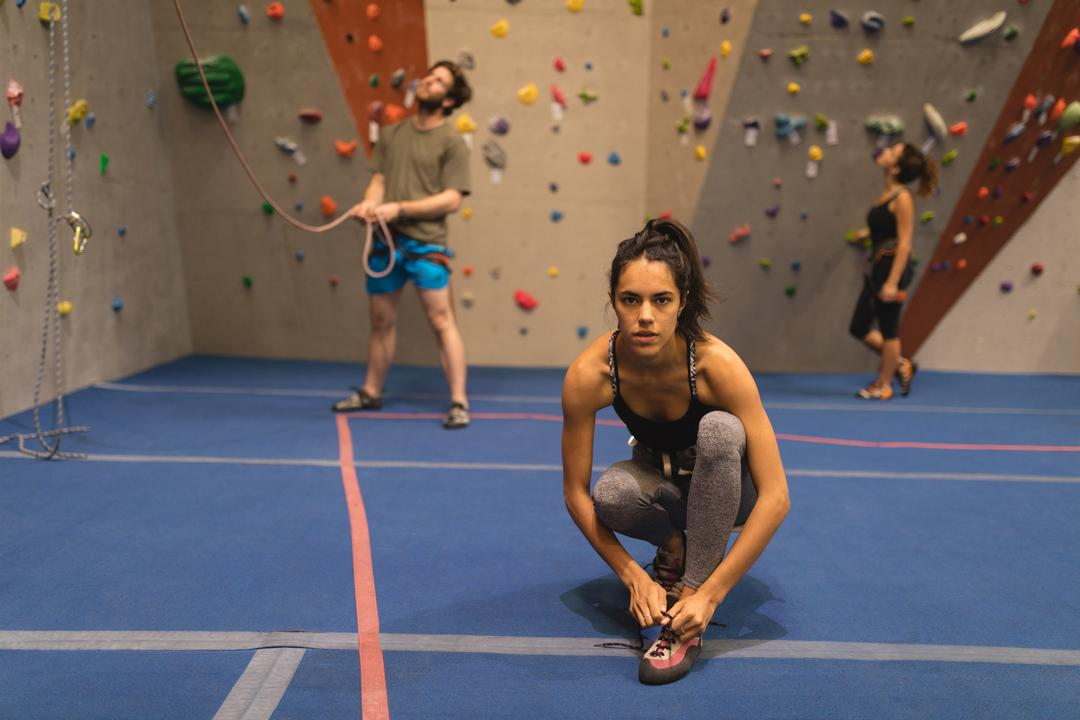 Portrait of woman tying shoelace while athletes climbing wall in background at gym Free Stock Images from PikWizard