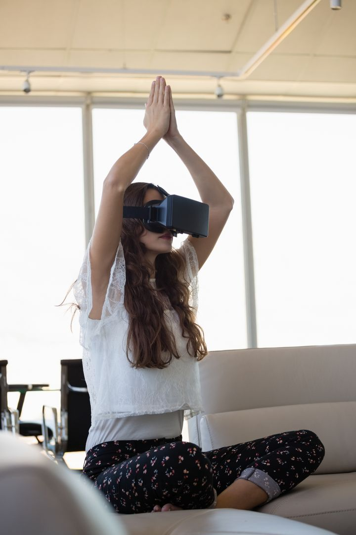 Young businesswoman mediating while using virtual reality on sofa in office Free Stock Images from PikWizard