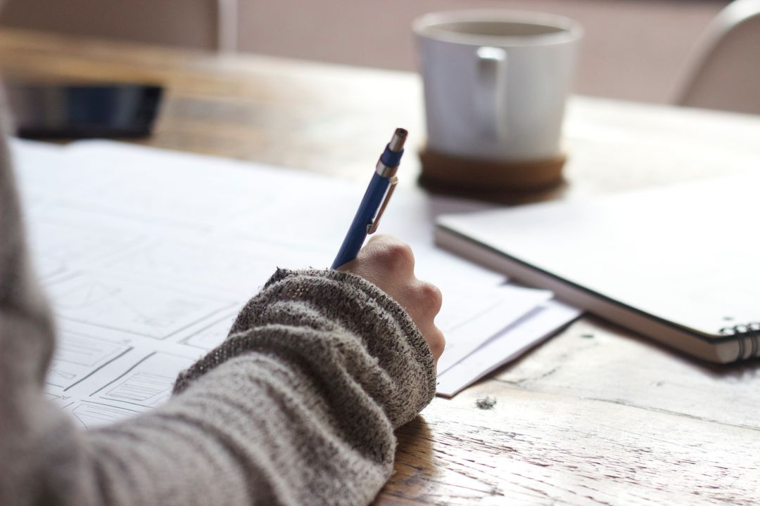 Image of a Person Holding a Pen and Writing Something Down