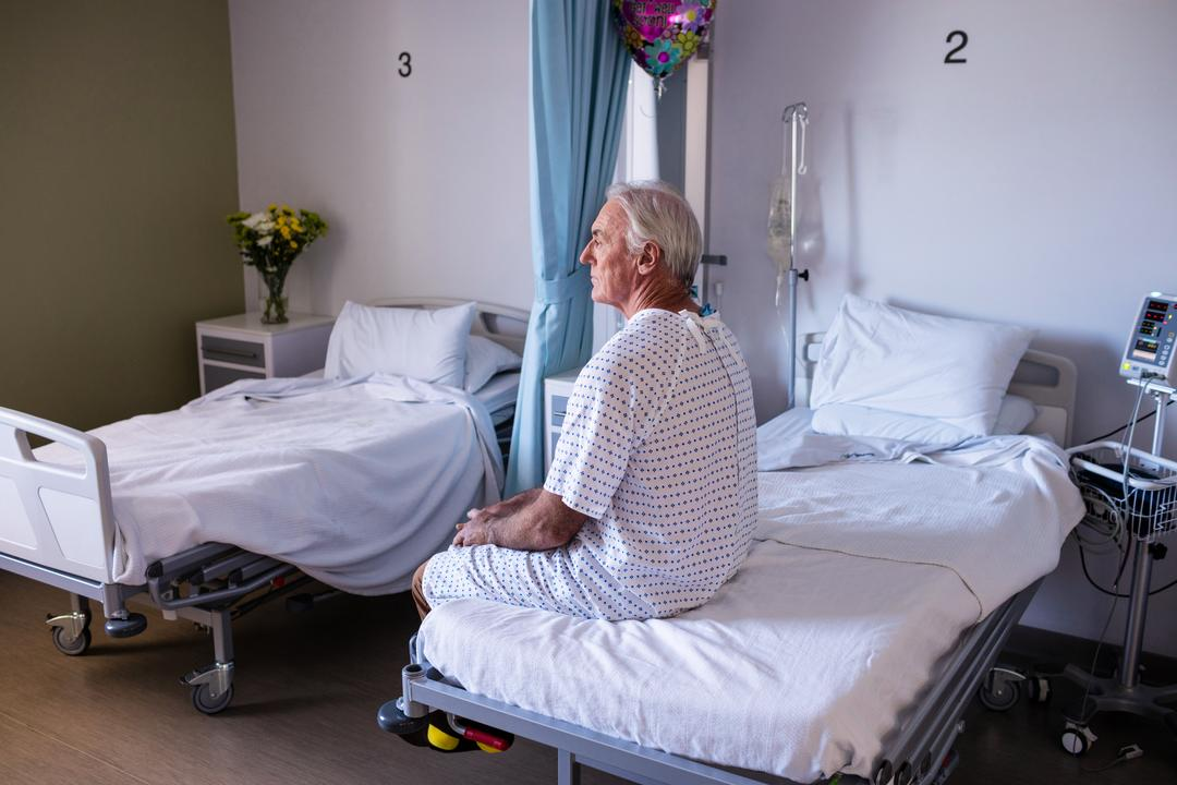 Thoughtful male senior patient sitting in the ward at hospital Free Stock Images from PikWizard