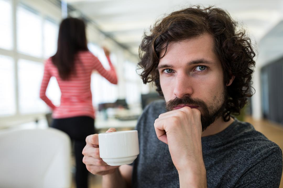 Portrait of male graphic designer holding a cup of coffee in office