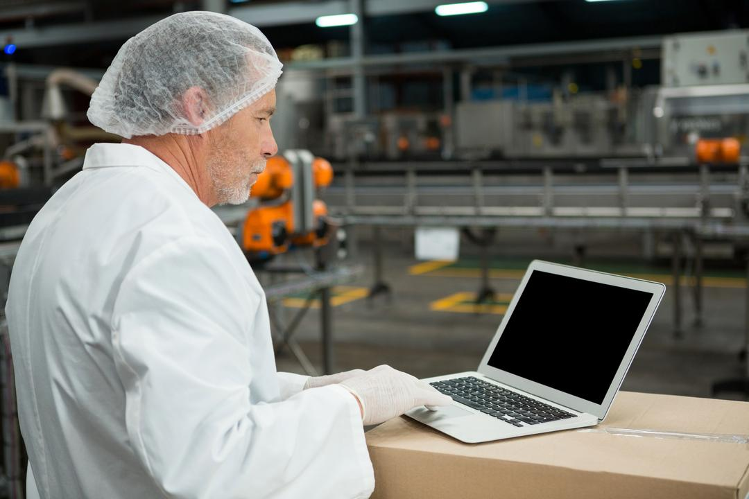 Side view of male worker using laptop in cold drink factory Free Stock Images from PikWizard