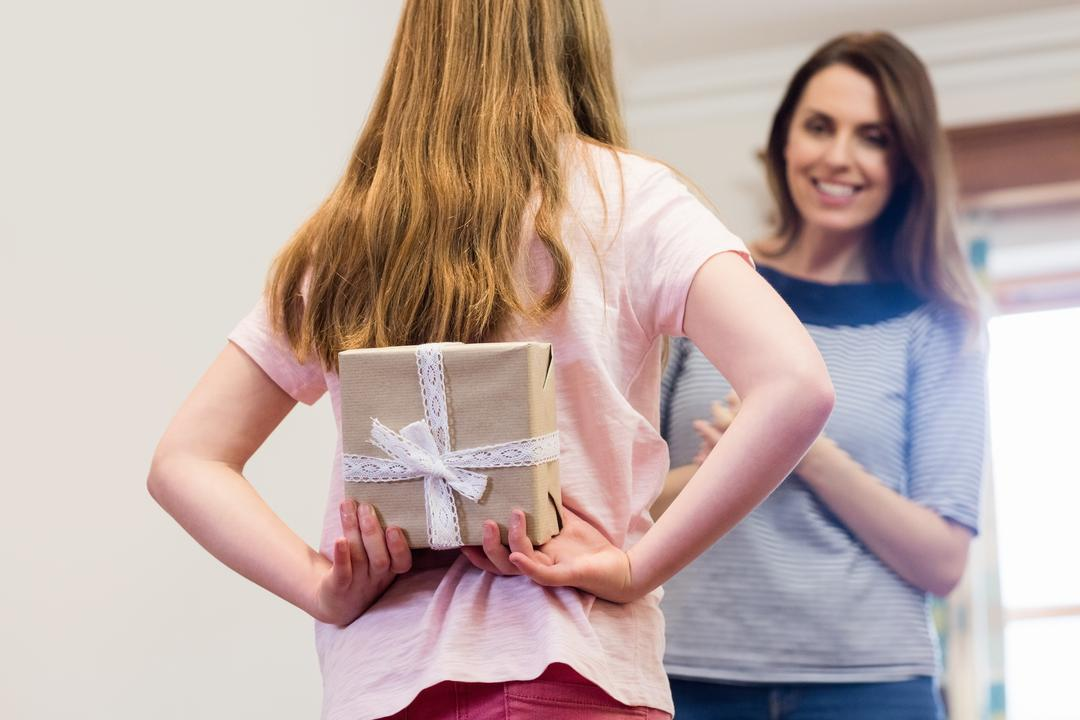 Daughter hiding gift box behind her back from mother in living room