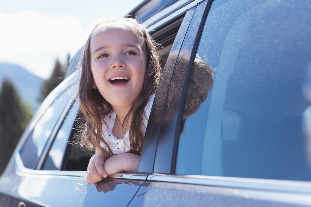 Cute girl looking out of the car window on a sunny day Free Stock Images from PikWizard