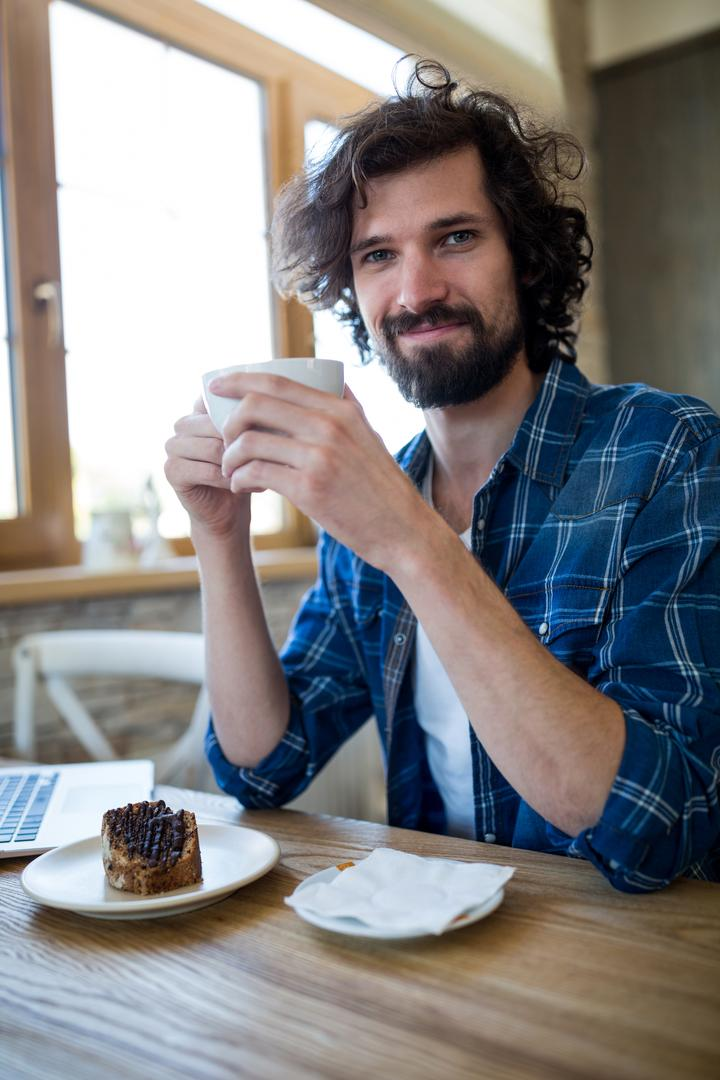 Portrait of smiling man having coffee and pastry in coffee shop