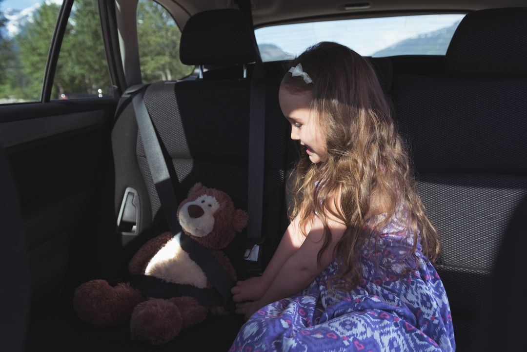 Cute girl tying a teddy bear with seatbelt in car Free Stock Images from PikWizard