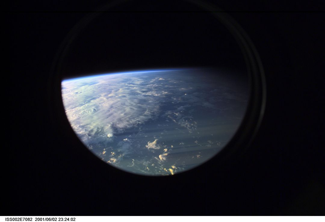 ISS002-E-7082 (2 June 2001) --- Earth's limb at sunset as photographed by one of the Expedition Two crew members with a digital still camera aimed through the nadir window of the U.S. Laboratory Destiny.  Beneath the limb, a large mass of clouds fills the window.