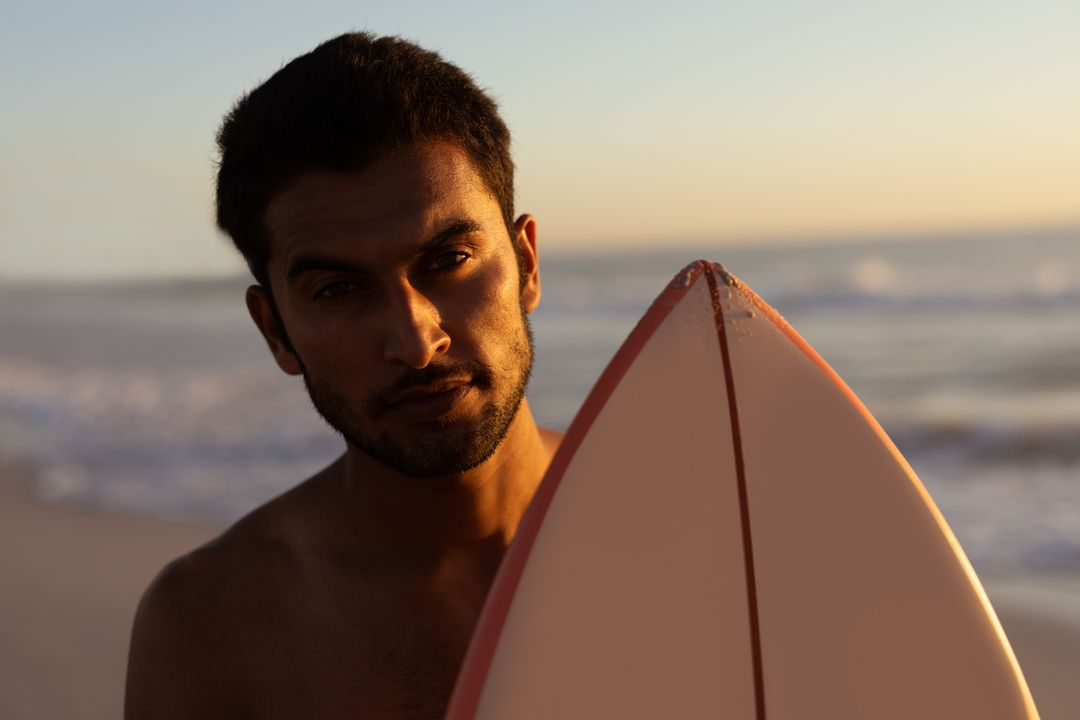 Portrait of man standing with surfboard on the beach