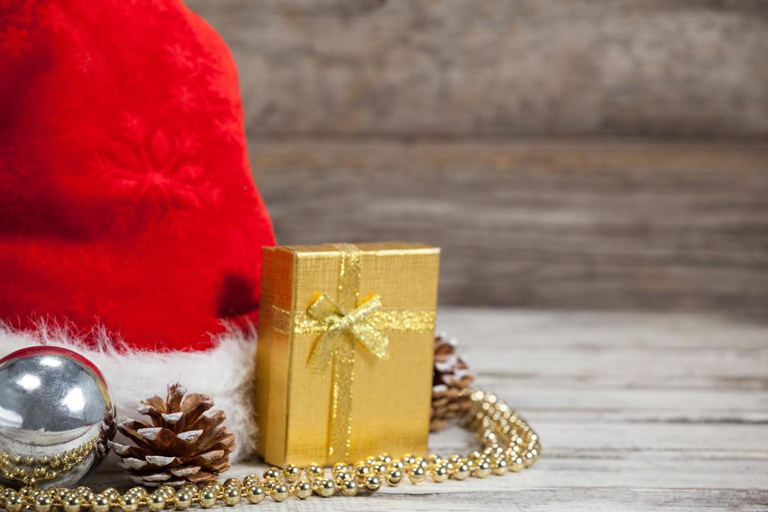 Close-up of Christmas decoration, gift and santa hat kept on wooden table during Christmas time Free Stock Images from PikWizard