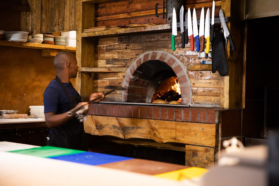 Chef baking a pizza in a wooden-burning oven