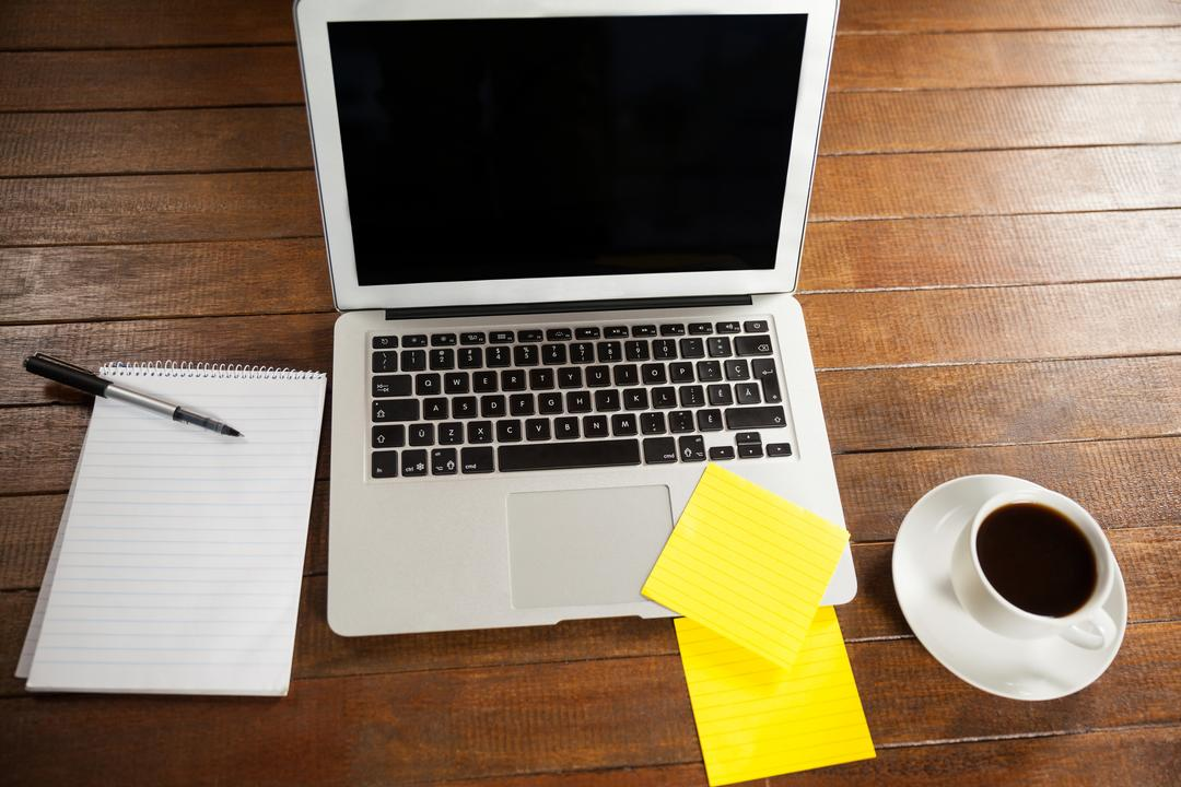 Office desk with laptop, notepad and cup of coffee in office Free Stock Images from PikWizard