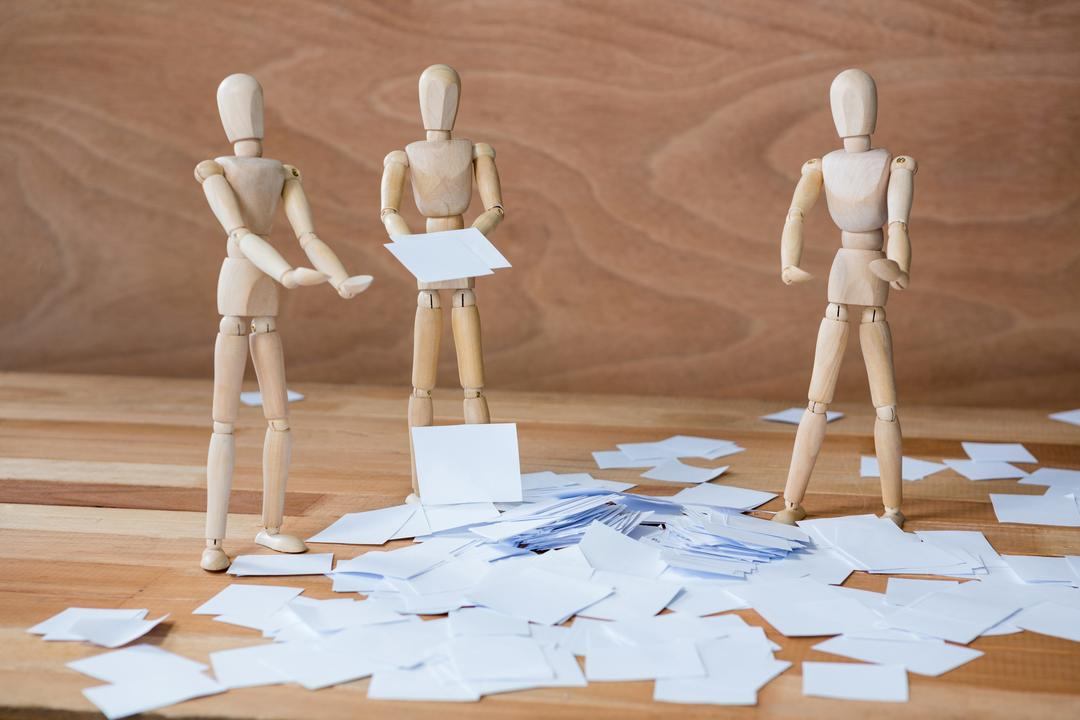 Conceptual image of figurine standing around scattered of paper