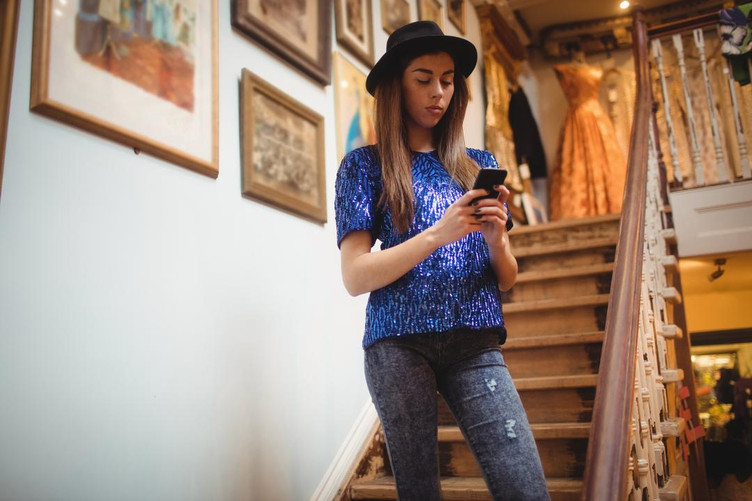 Female staff using mobile phone on staircase in boutique store