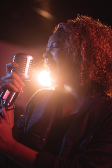 Woman singing on retro microphone in recording studio