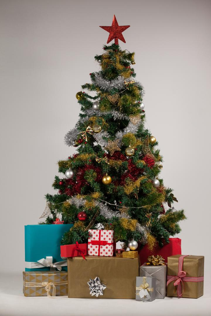 Various presents and christmas tree arranged on white background during christmas time
