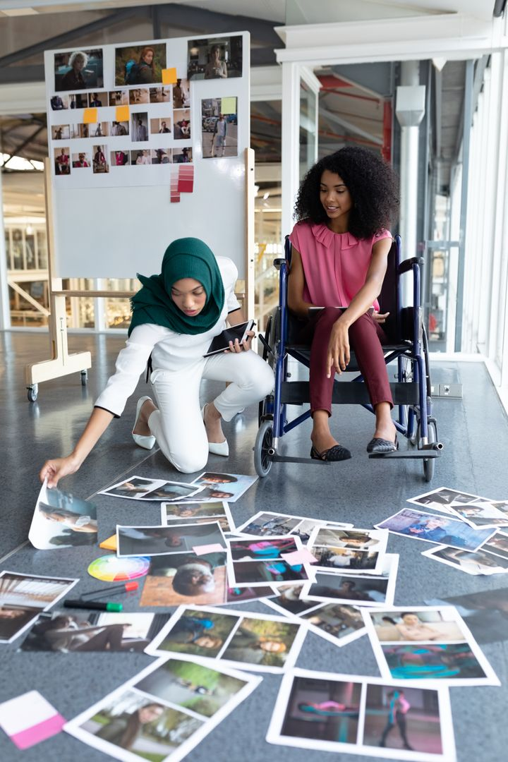 Front view of young diverse female graphic designers looking at photographs in office. This is a casual creative start-up business office for a diverse team