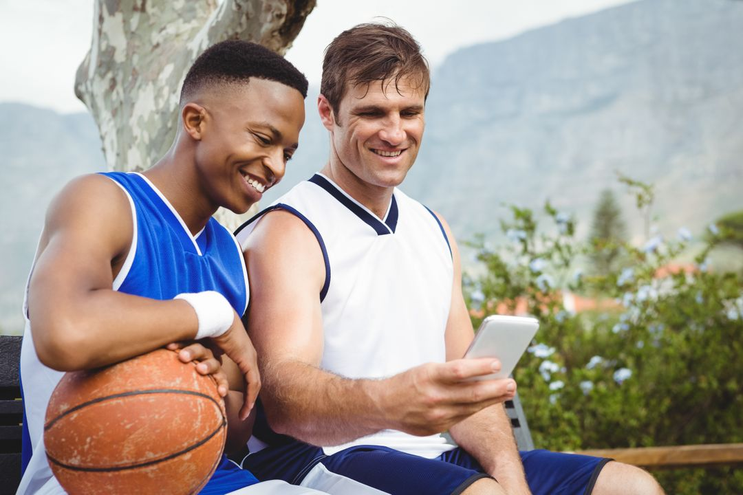 Two basketball players smiling looking a smartphone